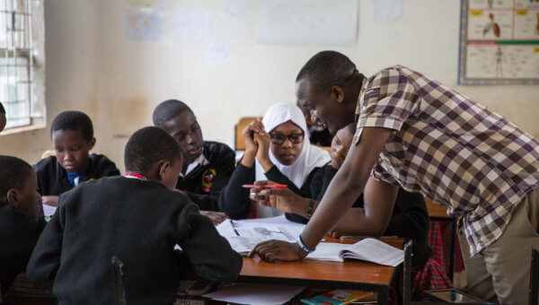 Students working with their mentor at Marangu Hills Secondary School in Tanzania
