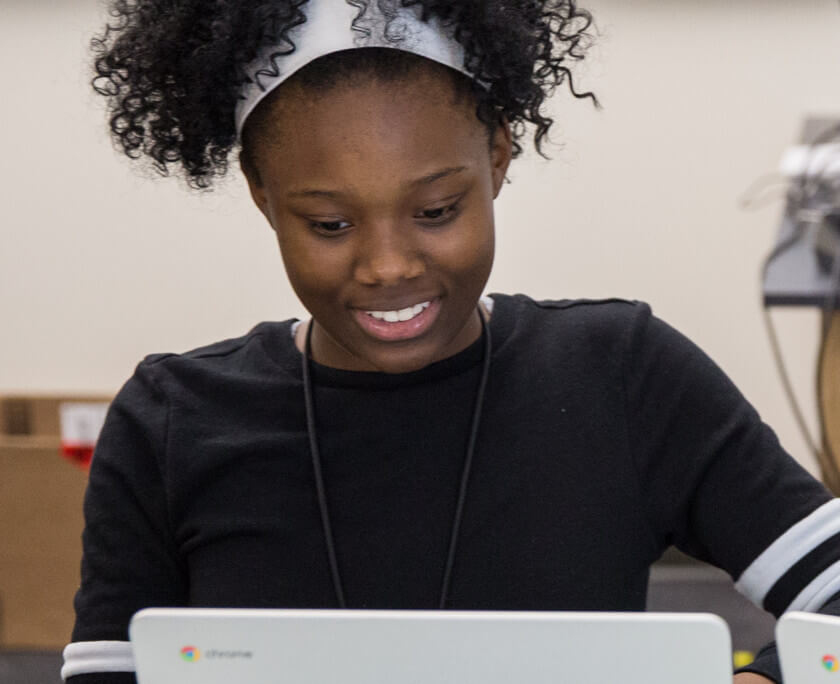 Student smiling at a laptop