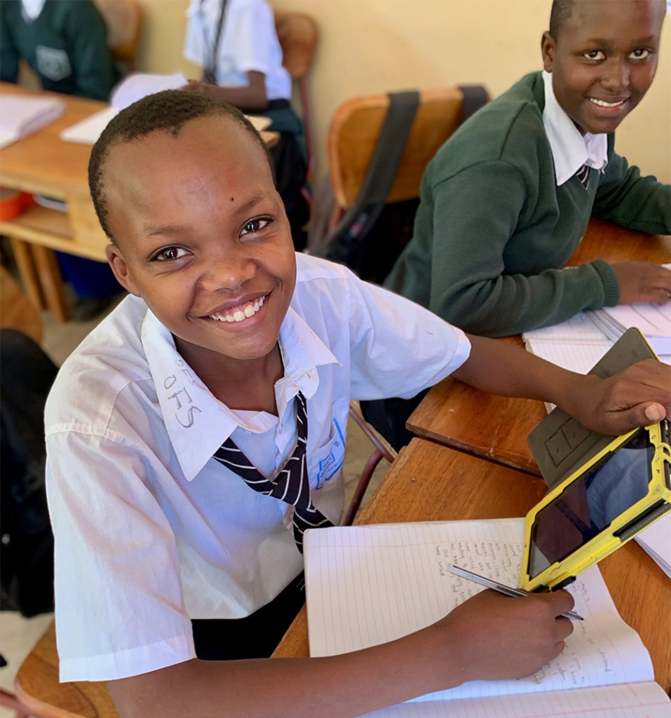 A smiling Mtakuja student holding a Quest Forward tablet.