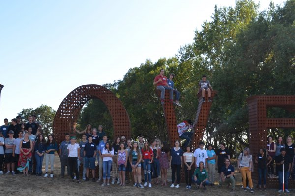 """Students from Quest Forward Santa Rosa pose in front of a large iron sculpture that spells out """"Love"""""""