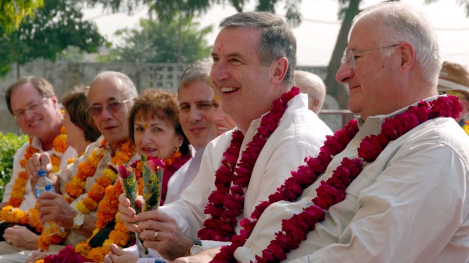 Joe Rickets and Alan Barkley sit next to each other. They wear all white with red leis draped around their necks.
