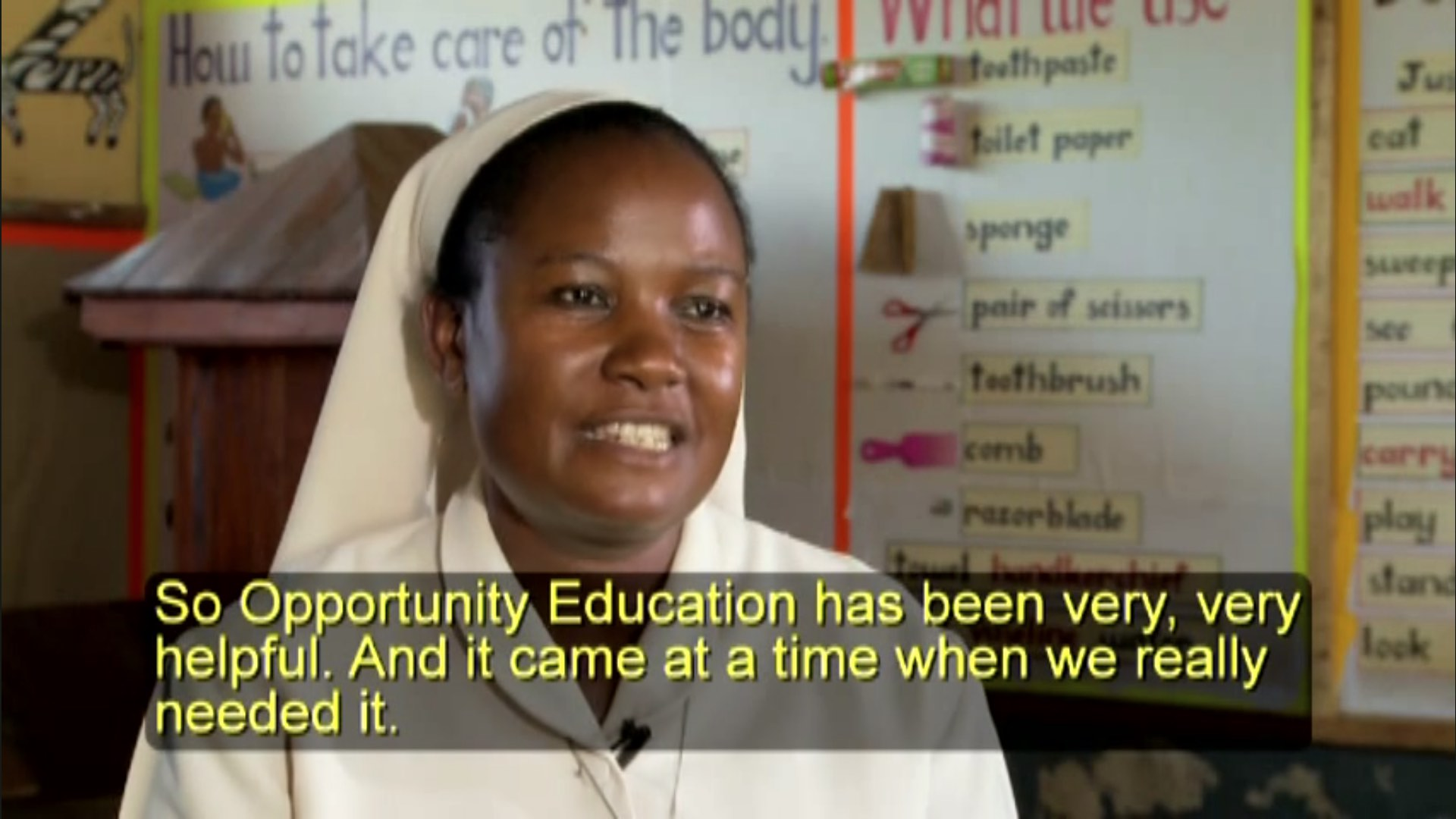 "A screenshot from the video ""Schools of Hope"" showing a woman in white garb. The closed captioning says ""Opportunity Education has been very, very helpful. And it came at a time when we really needed it."