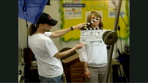 A woman stands in front of a camera. To her right is a man holding a clapperboard in front of her.