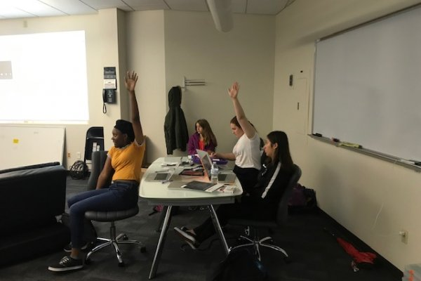 Four students sit around a table during Career Bootcamp. Two of them are raising their hands enthusiastically.