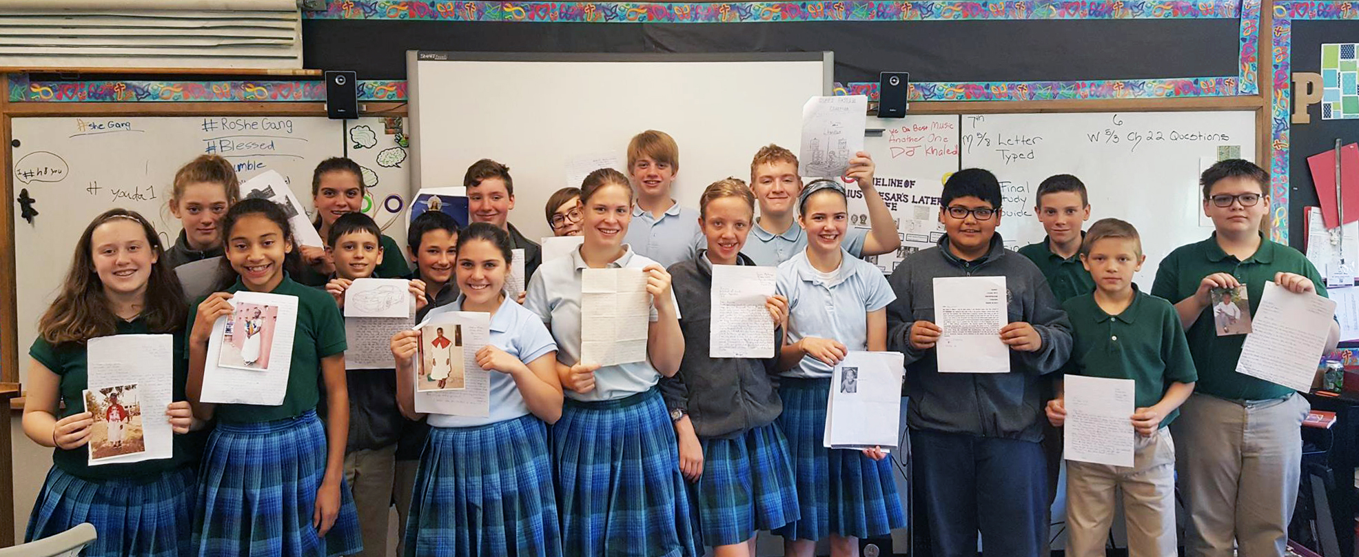 A class of students proudly display their pen pal letters.