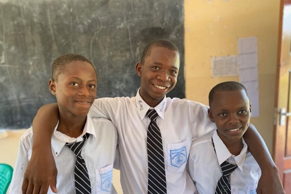 Three students stand together, smiling at the camera. The middle student has his arm around the two students on either side of him.