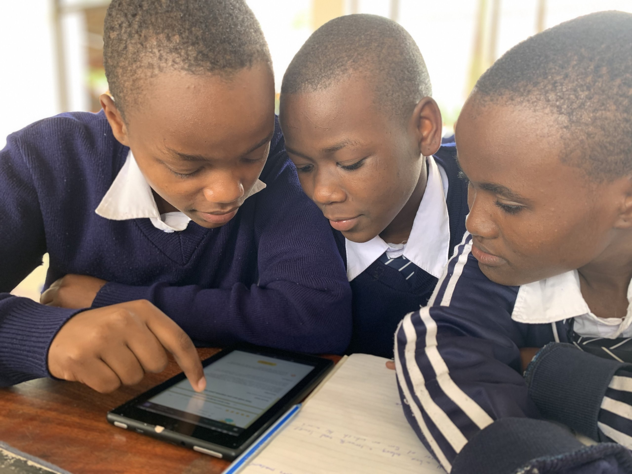 Three students gather around a tablet to read what's on the screen. The student on the left hand side points to something on the screen with his index finger.