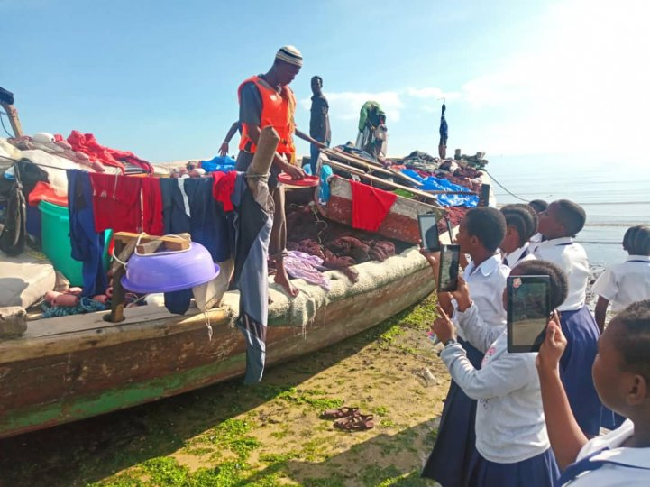 Students from St. Monica Secondary School in Zanzibar gather around a fishing boat as a man on the boat shows them fishing gear. Some of the students use tablets to take pictures of the demonstration.