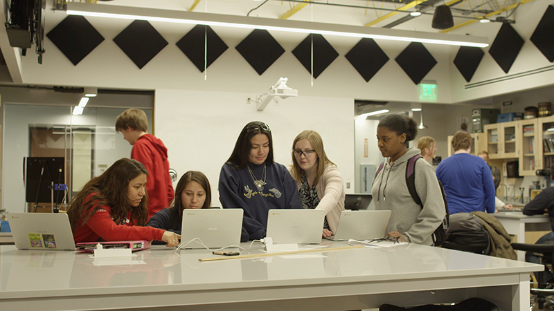 Students and a mentor work intently in Quest Forward Academy Omaha's state-of-the-art science lab.