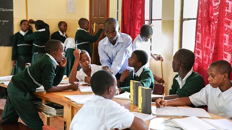 A group of Tanzanian students gather around a table. Some listen to their mentor who is perched on the end of the table talking, while others work on their tablets.