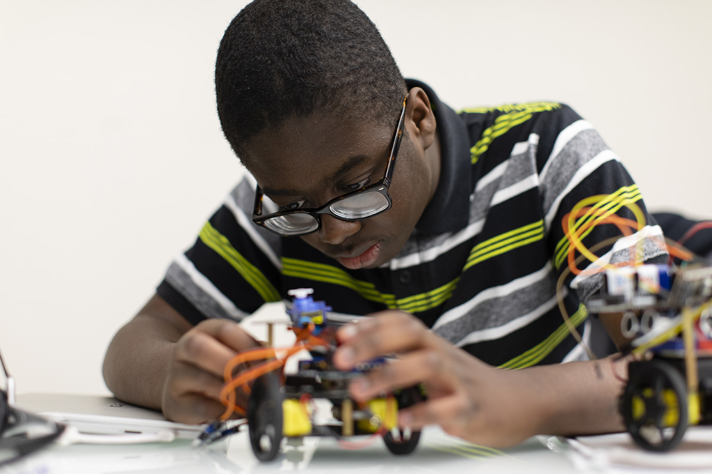A student in a striped collar shirt leans over the table in front of a complicated and colorful robot. He is actively learning by creating the robot himself.