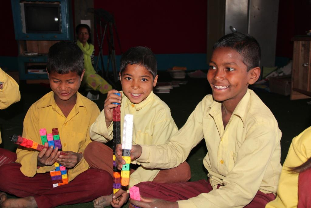 Three young students in Nepal sit and play with colorful blocks. They were a part of Opportunity Education's Primary Program.