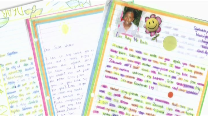 3 pages of brightly decorated letters spread out. The top letter has a picture of a student and a smiley face sticker.