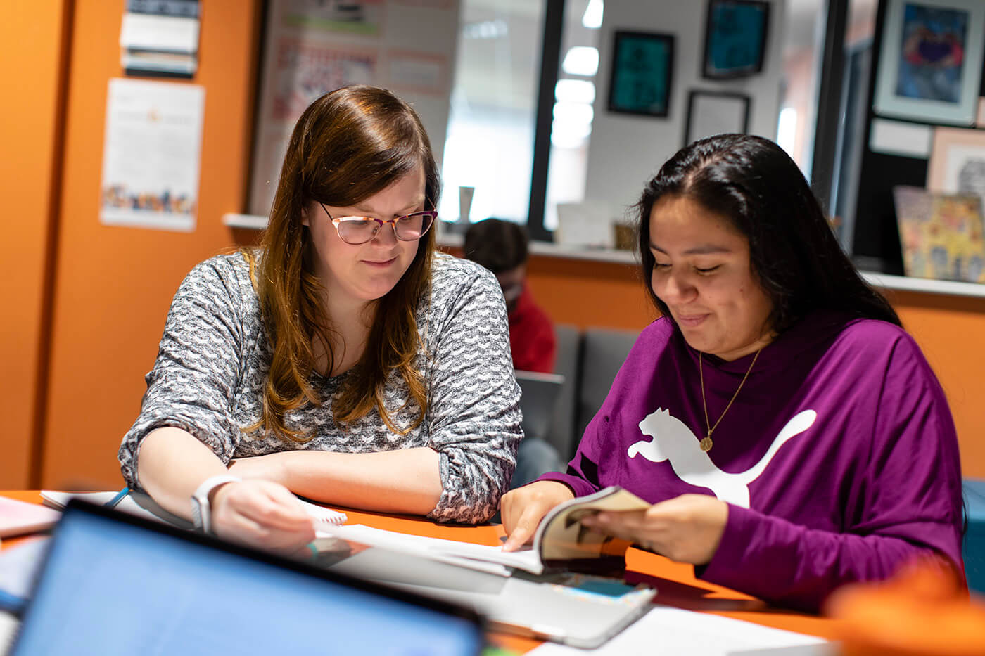 A student and a mentor sit together at a table reviewing a book at Quest Forward Academy Omaha.