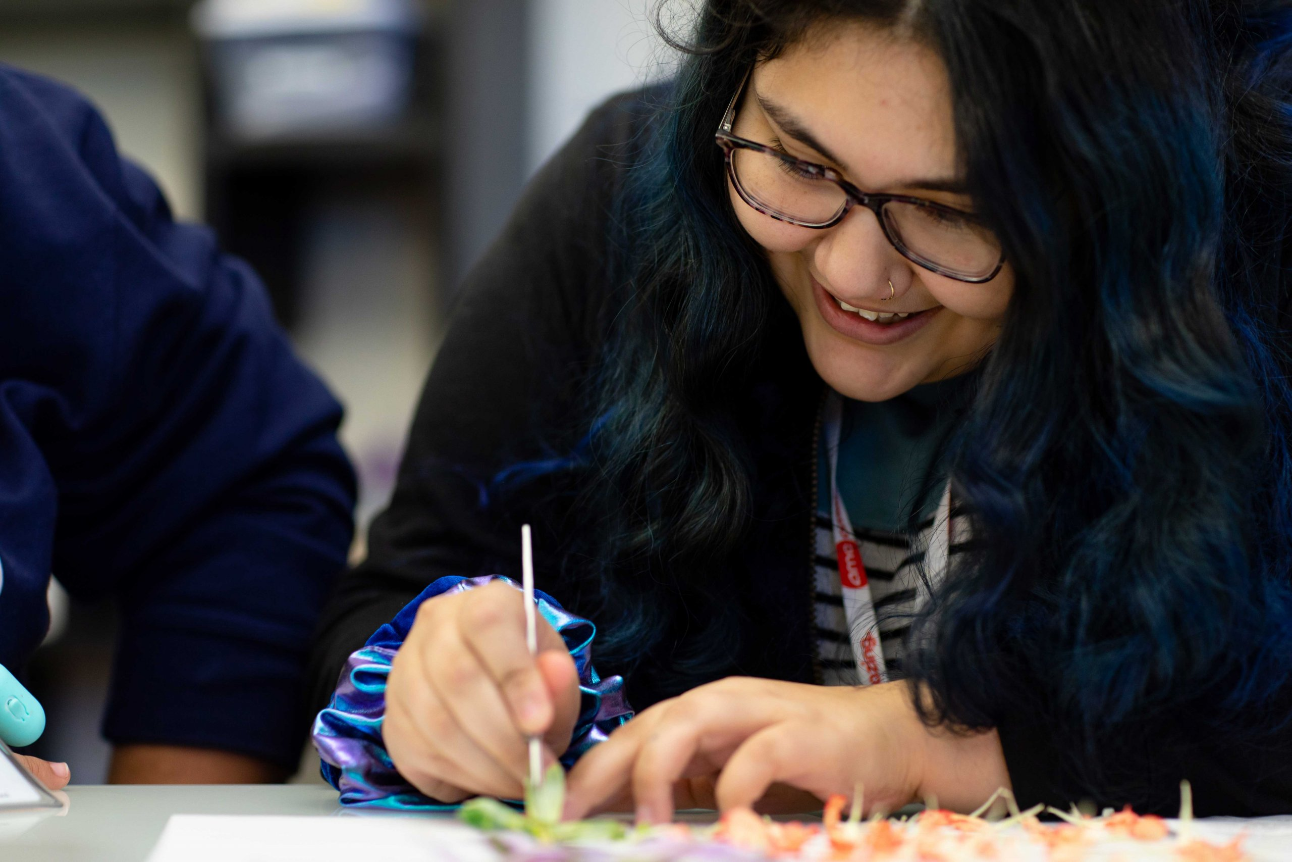 A smiling student uses a scalpel to cut apart a flower. The dissected stem and petals are laid out in front of her.