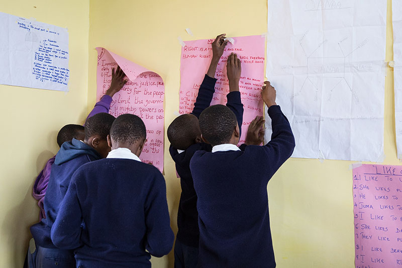 Students in Tanzania work together to hang up handwritten posters on the walls.