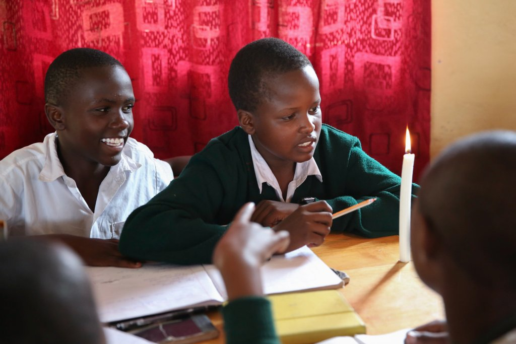 A group of four students observe a lit candle as they work on a quest.