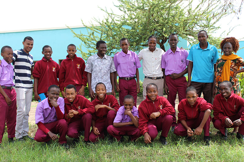 Students and staff at Arusha City Boys pose outside. The students wear red slacks and either a lavender or red shirt.