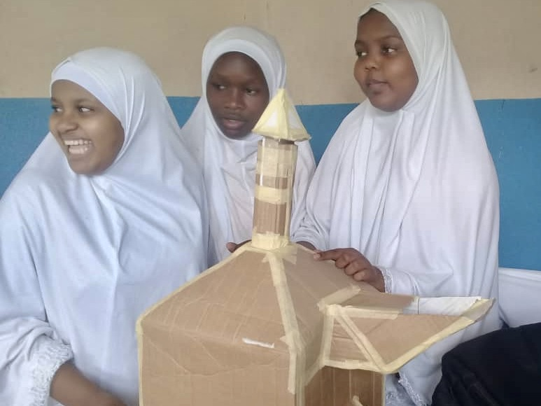 Three students at Mbarali Preparatory School post with a structure they made out of cardboard and tape.