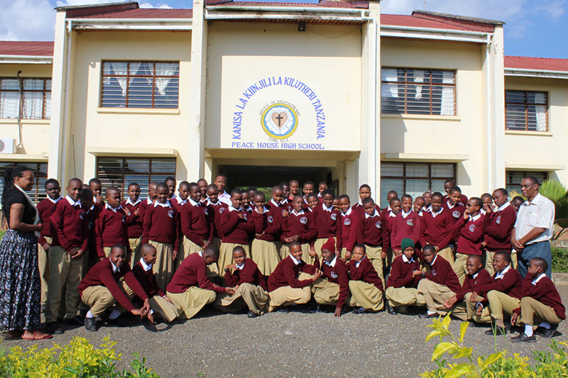 Students in uniforms pose outside Peace House High School in Tanzania.