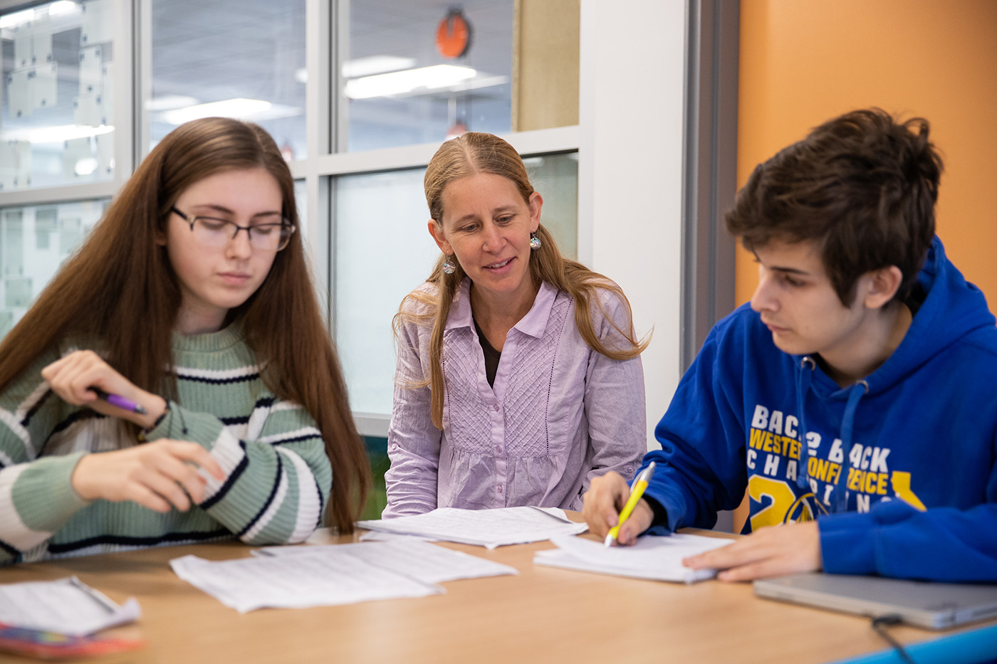 Dana Gundling sits between two students, smiling as they work.