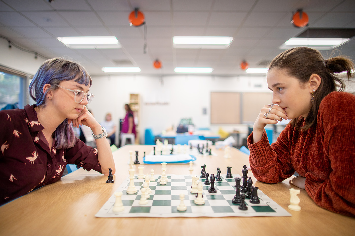 Mentor Sarah Weinstein sits across the table from a student. In between them is a chess board. Sarah stares at the board, thinking intently, while the student stares at Sarah.