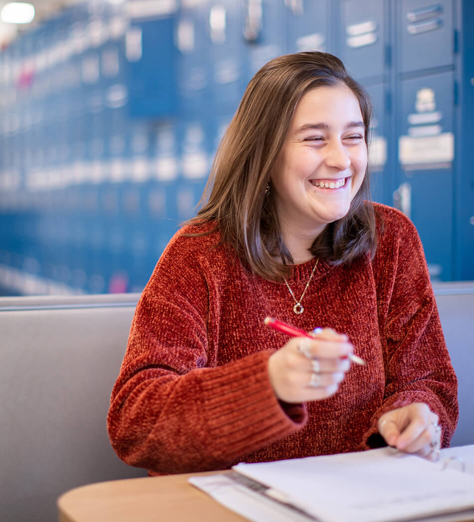 A Quest Forward Academy student has a big smile while writing in a notebook.