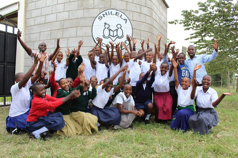 Students at Shilela Secondary School pose together outside the school, smiling and cheering with their arms extended.