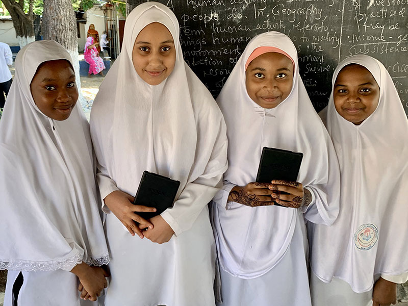 Four students in hijabs smile at the camera. The two girls in the middle hold tablets.