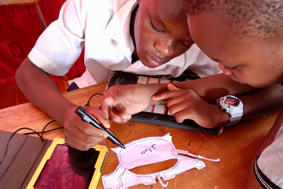 Two secondary school students collaborate on a project. One holds a marker and is writing on paper that has been cut out into a design.