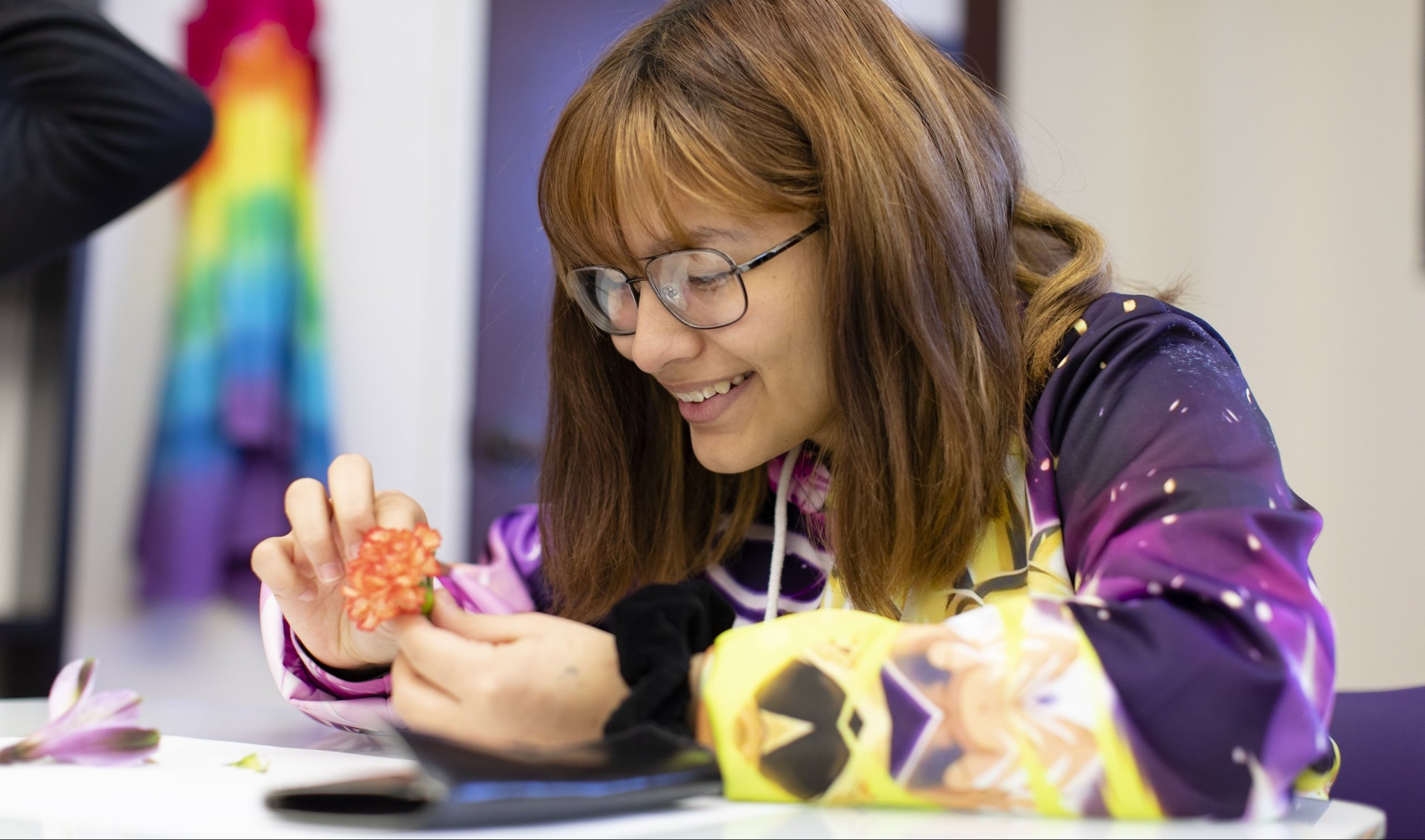 A Quest Forward Academy student smiles while dissecting a flower in a bright classroom.