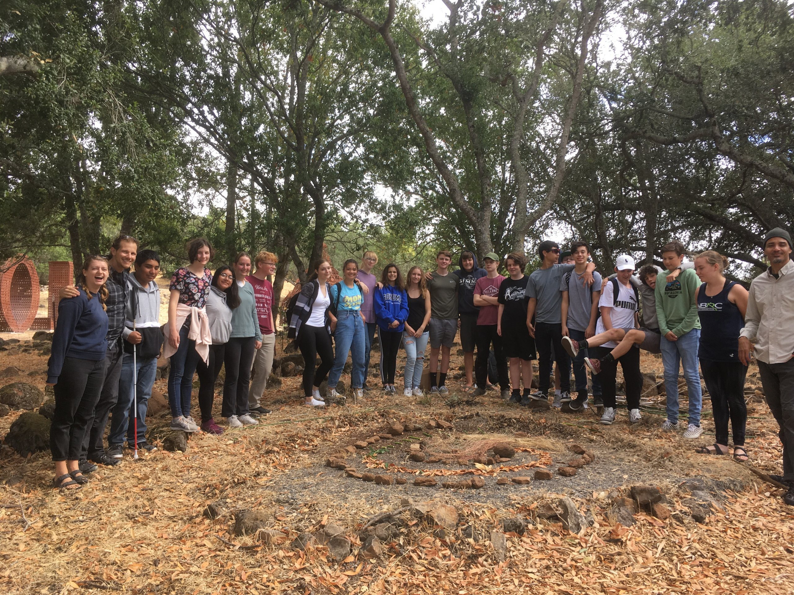 Quest Forward Academy Santa Rosa students standing proudly in front of a land art sculpture they created on a trip.