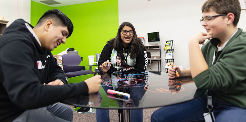 Three Quest Forward Academy Omaha students sit together, smiling at a small, glass table with dry-erase diagrams written on it.