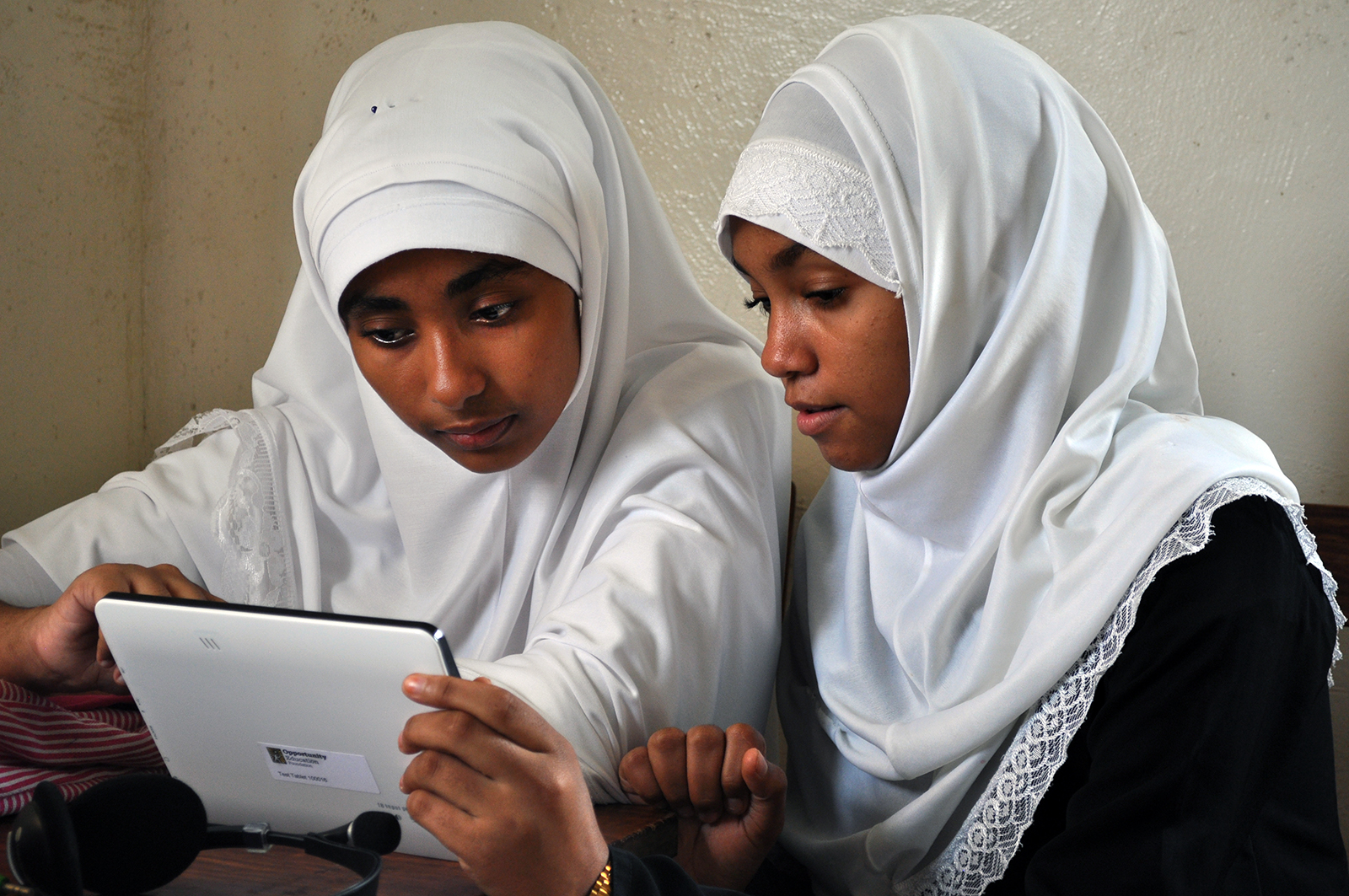 Two Zanzibar students work together in class holding an Opportunity Tablet, provided by Opportunity Education.