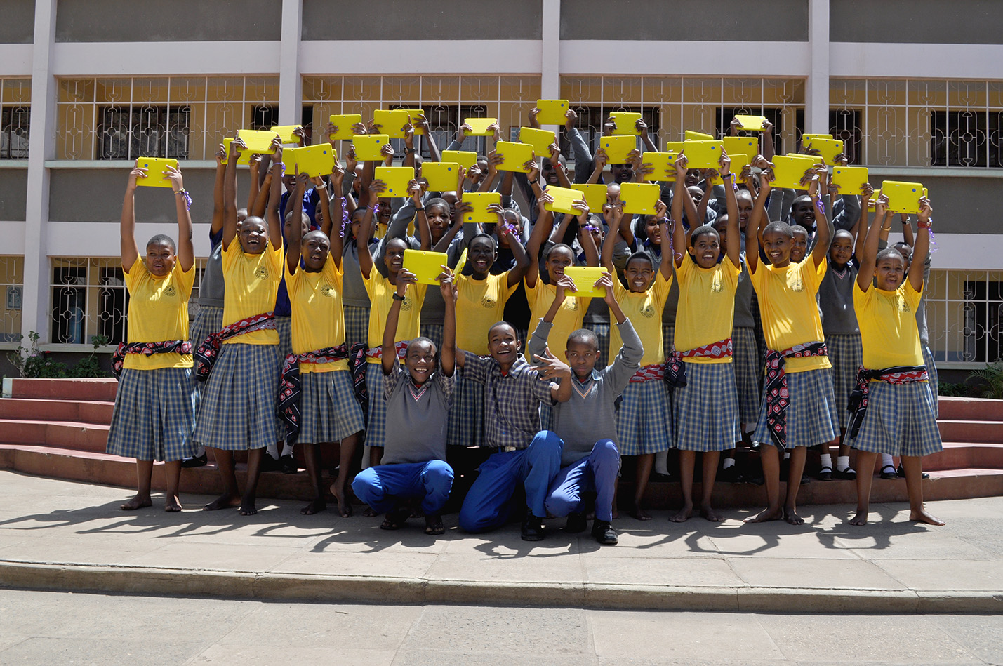 A class of students smiles while proudly holding their bright yellow Opportunity Tablets high.