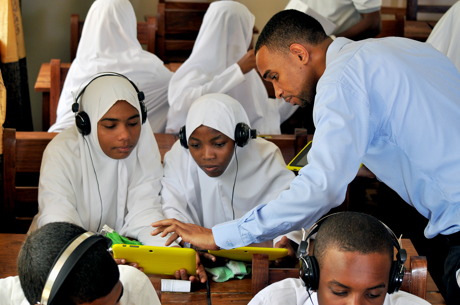 A Zanzibar classroom of students using Opportunity Tablets, provided by Opportunity Education, while a teacher works with two students, tapping the screen of their tablet.