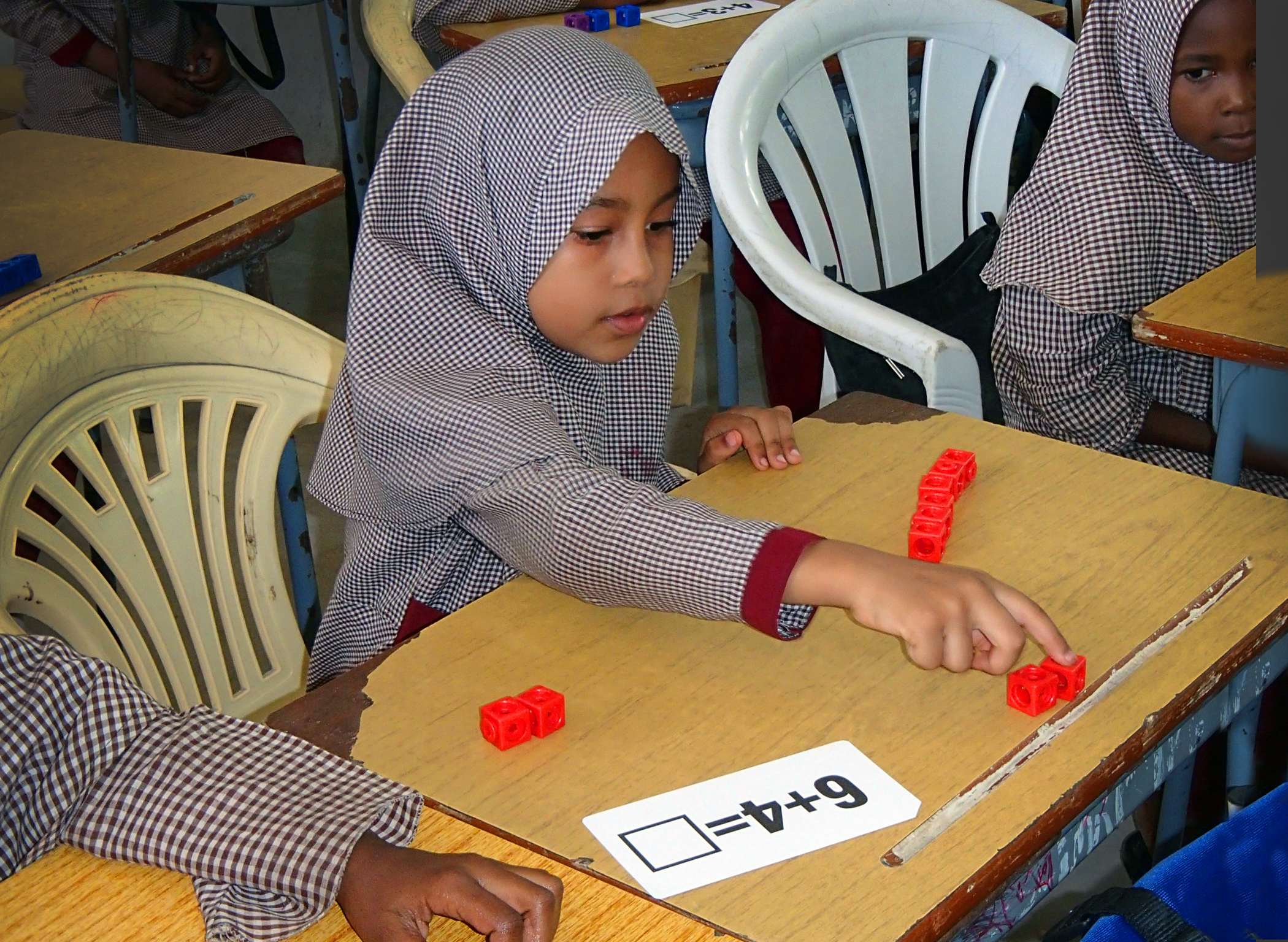 """A Primary Program student counts with blocks. In front of her is a card that reads """"6+4=[]."""""""