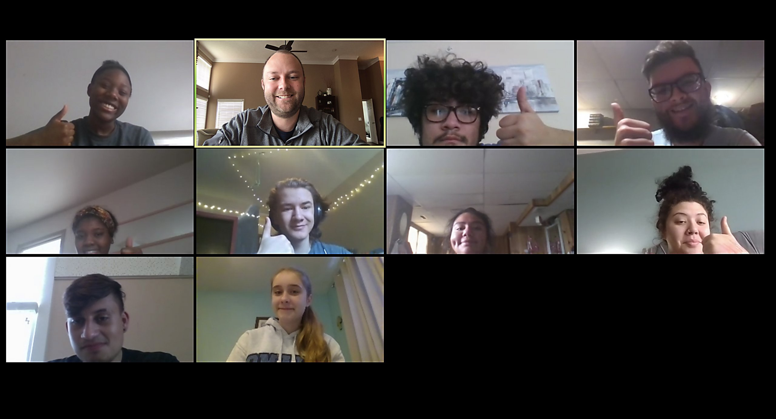 A screenshot of a Zoom call where students are distance learning during an English class. The students and the teacher all smile at the camera and give a thumbs up.