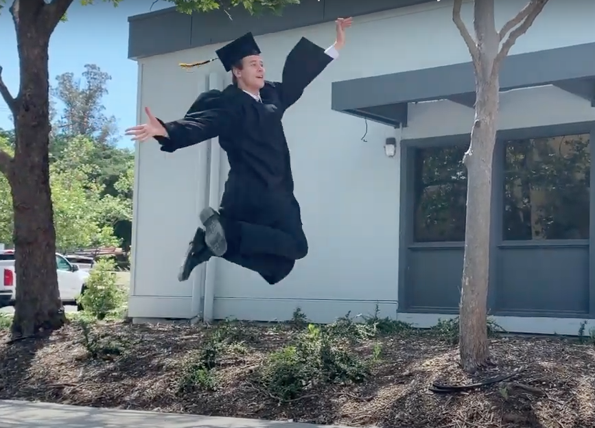 Graduate Max leaps for joy as he crosses the stage.