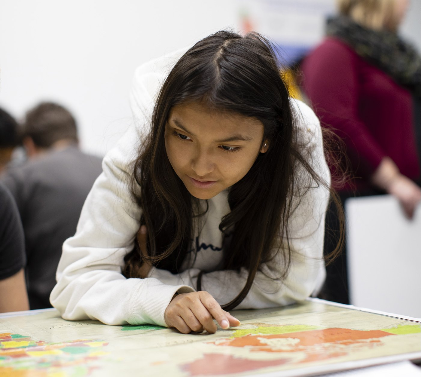 A student appears focused, pointing to a map on a tabletop.