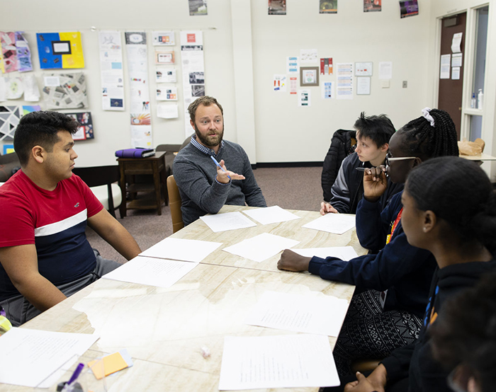 A mentor sits at a table with a group of diverse students, discussing a point with a student on the right.