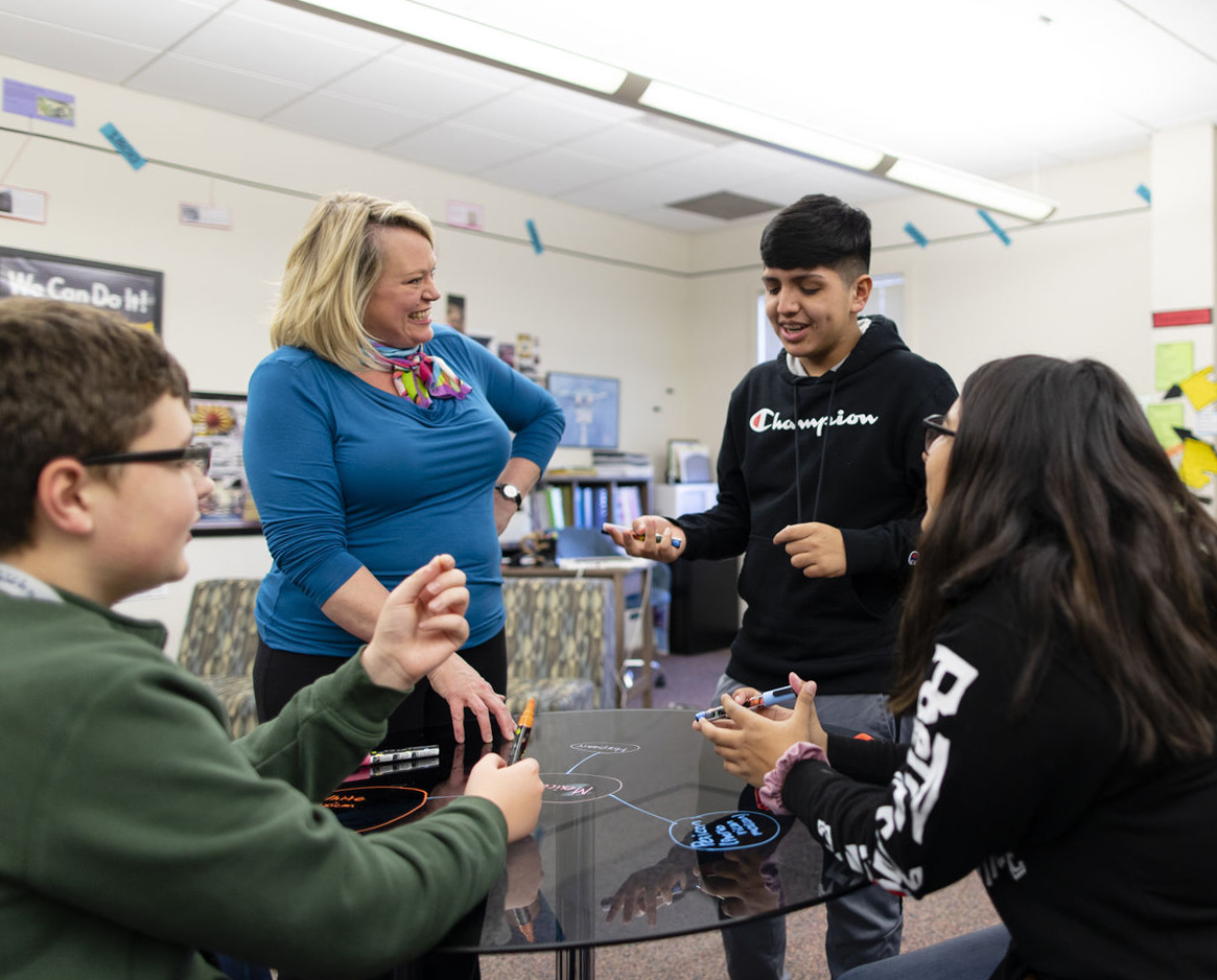 Students laugh with a mentor around a dry-erase table in a Quest Forward Academy Omaha classroom.