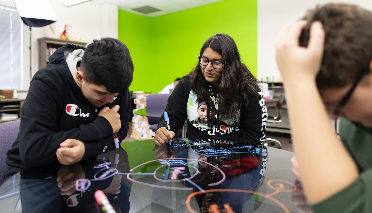 A student draws a diagram with a dry-erase marker on a glass tabletop, while two other students closely view her work.