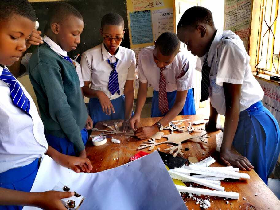 Four students appear deeply engaged in their work, assembling a a complex cardboard structure on a work table in a Quest Forward School in Tanzania.
