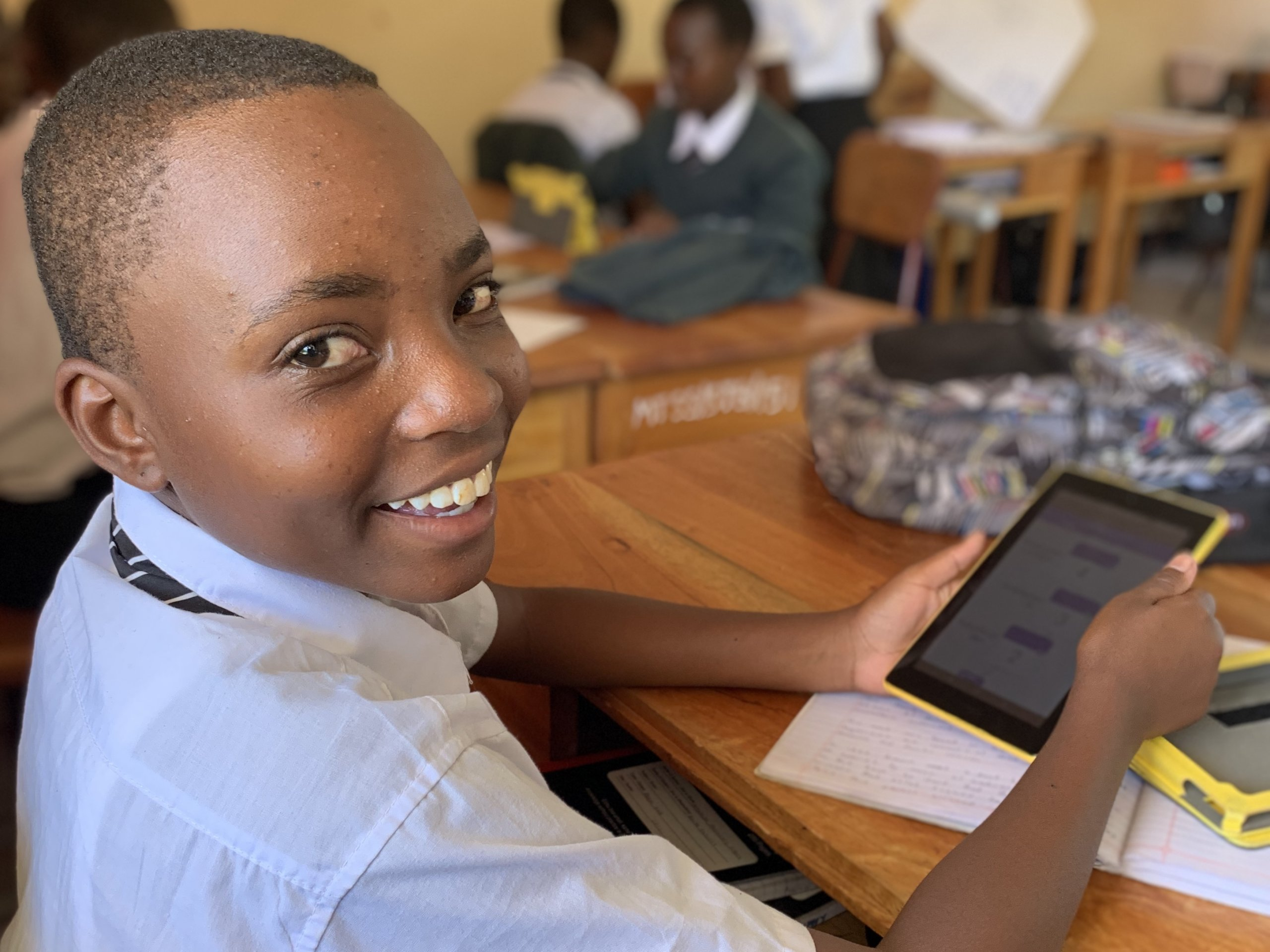 A student smiles brightly over his shoulder, while holding a tablet displaying the Quest app in his secondary school classroom in Tanzania.