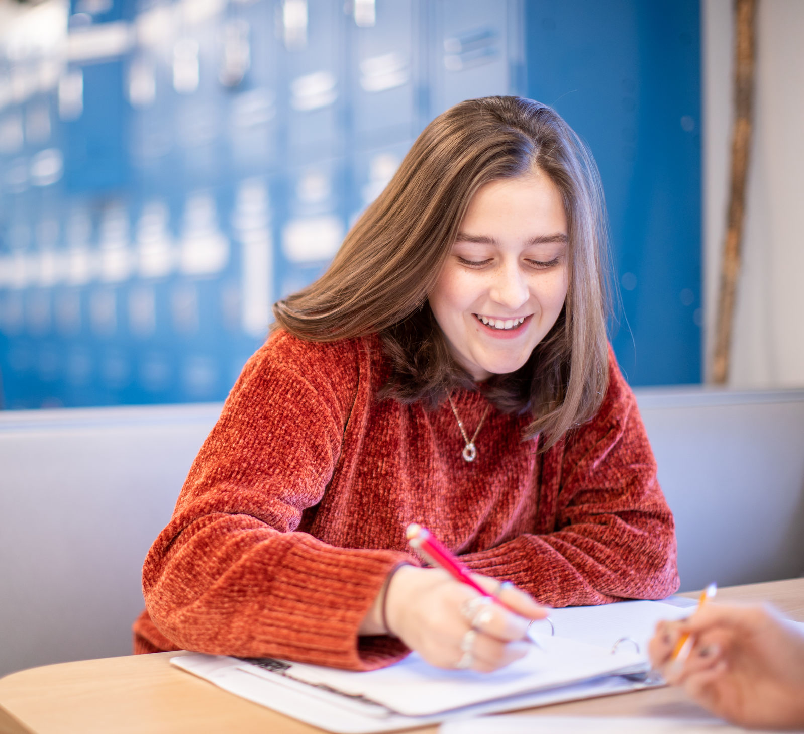 A student smiles broadly while writing in a math notebook at Quest Forward Academy Santa Rosa.