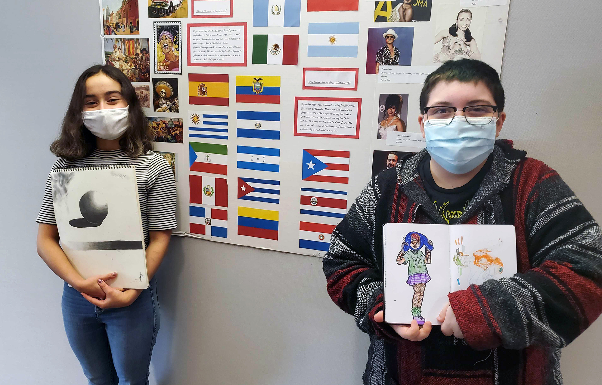 Two Quest Forward Academy Omaha students stand together displaying drawings from their college-level course at Bellevue University.