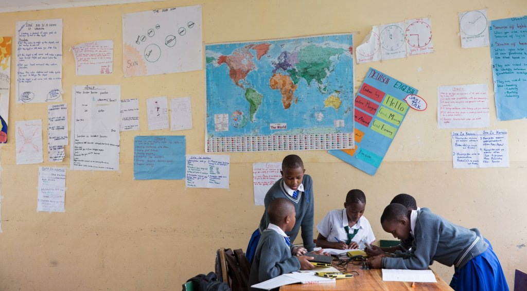 Student work covers the wall behind students working in a secondary school classroom in Tanzania.