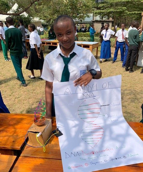 A student at Mtakuja Secondary School displays the DNA model she constructed.