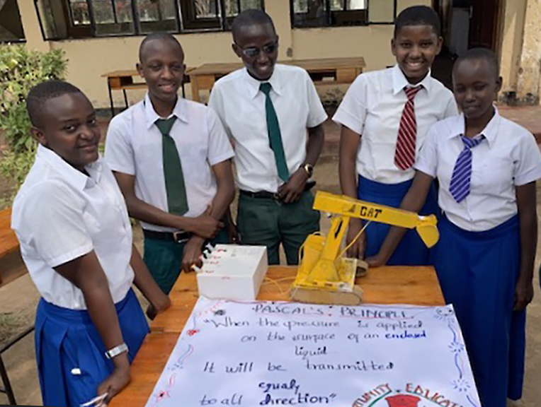 Students from Mtakuja Secondary School display an artifact demonstrating Pascal's Principle of hydraulics.